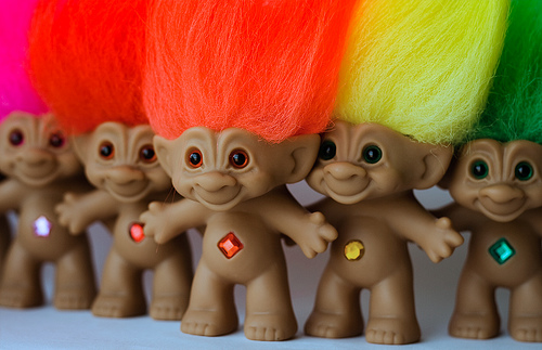 A selection of troll toy dolls with pink, red, orange, yellow and green coloured hair and jewels in their bellys