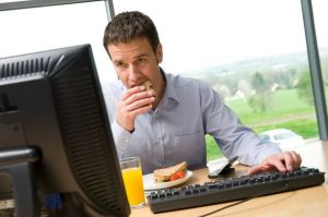 man having lunch at desk