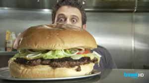 man vs food presenter adam richman hides behind a giant burger